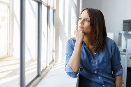 Thoughtful woman staring out of a large window in an office or apartment on a sunny day resting her chin on her hand