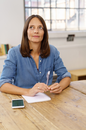 Businesswoman or mature student sitting thinking with a pen, paper and mobile phone staring up into the air as she puzzles a problem or searches for an answer