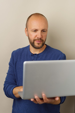 Businessman using a laptop on the move balancing it on his arm as he browses the web against a neutral studio background with copy space