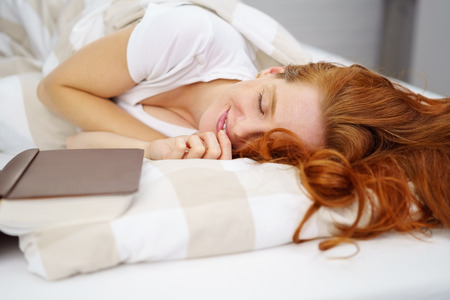 Young cheerful red-haired woman lying with book in bed Reklamní fotografie