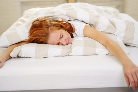 Exhausted young redhead woman sleeping spread out on the bed sprawled over the pillow under a warm duvet Stock Photo
