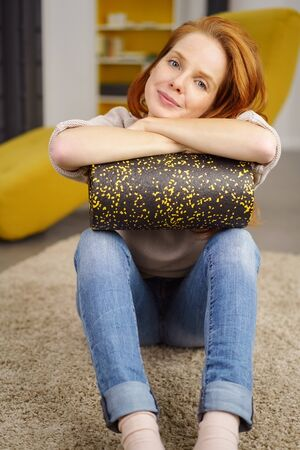 Portrait of young woman sitting on floor with exercise foam roller