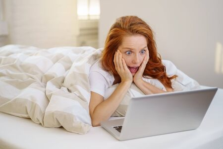 Astounded young woman reacting to news on the web or internet as she lies reading her laptop under a duvet on her bed