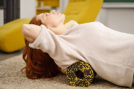 Young red-haired woman exercising on floor with foam roller