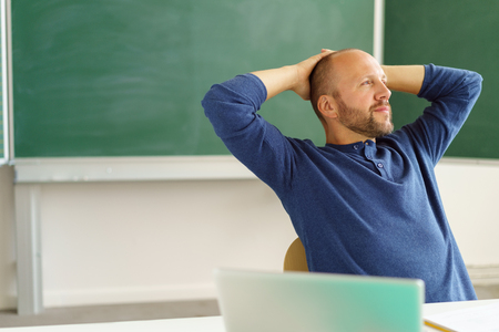 Teacher or creative designer taking a break to lean back in his chair with his hands behind his head and a chalkboard background