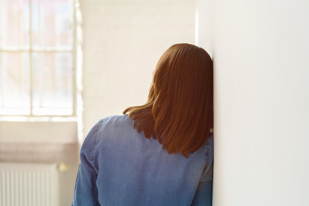 Rear view of long-haired woman leaning against white wall Reklamní fotografie