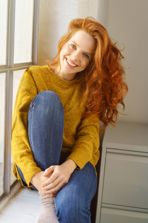 Vivacious pretty redhead woman relaxing on a window sill in her jeans and socks giving the camera a warm beaming smile