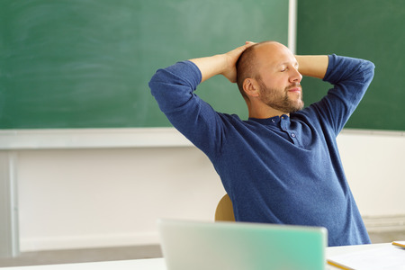 Tired male teacher relaxing in his chair in the classroom with his hands behind his head and eyes closed