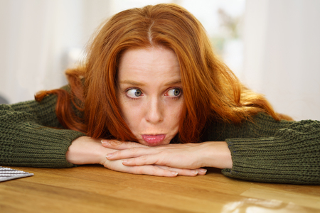 Sulky young woman pouting her lips as she leans her chin on her folded arms on a wooden table Stock Photo