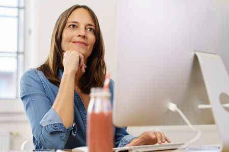 Attentive businesswoman sitting listening to someone off frame with her hand to her chin and a smile Stock Photo