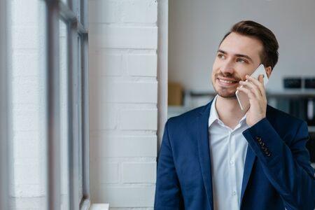 Joven empresario hablando por un teléfono móvil mientras está de pie junto a una ventana mirando con una sonrisa