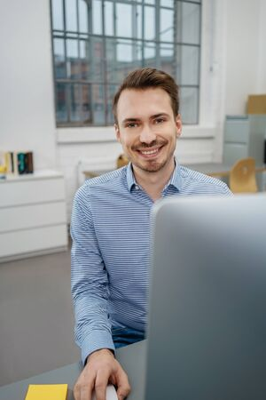 Happy friendly young businessman with a beaming smile sitting working on a large desktop monitor in an office
