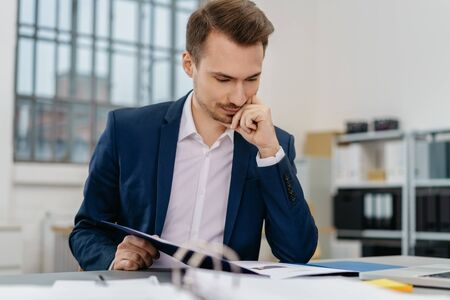Young man reading files while sitting at desk in office