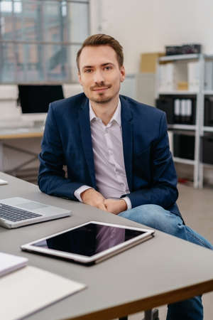 Businessman sitting at a table in an open plan office looking intently at camera with a quiet smile Stock Photo