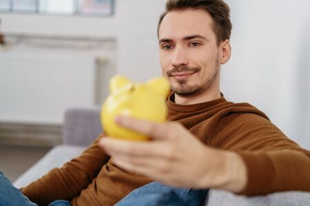 Young man sitting on sofa with yellow piggy bank