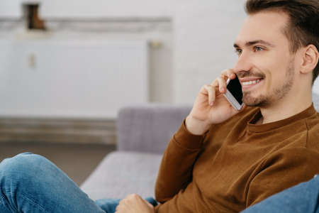 Young cheerful man talking on phone while sitting on sofa at home