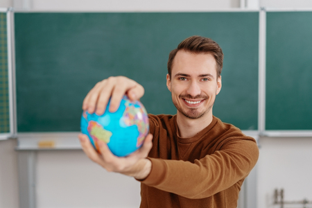 Portrait of young smiling man holding globe against blackboard in classroom