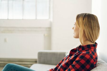 Lonely young woman sitting on a sofa in a bright white minimalist apartment turned away looking out of a window with copy space Stock Photo