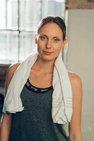 Pretty young female athlete in a gym standing looking thoughtfully at camera with a towel around her neck Stockfoto
