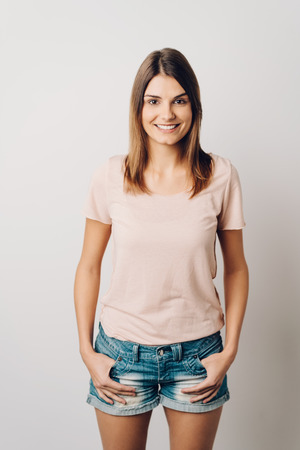 Trendy modern young woman in denim shorts standing smiling happily at the camera with her hands hooked into her pockets over a white studio background