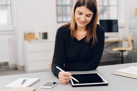 Happy businesswoman sitting working with a pen on a tablet at a desk in the office with a quiet smile of pleasure