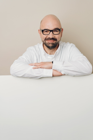 Smiling bald man in glasses leaning on white table with copy space