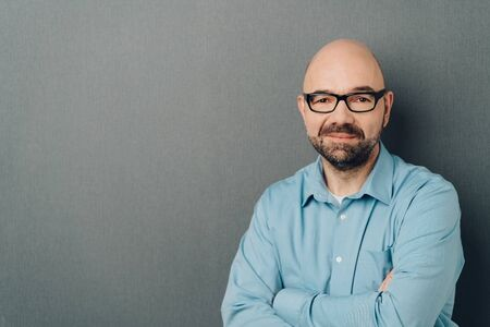 Upper body portrait of thoughtful bald businessman in blue shirt with arms folded