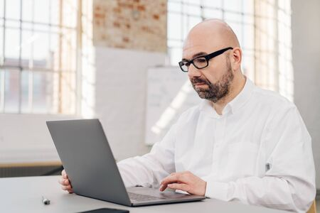 Unhappy businessman working on a laptop surfing the web with a focused serious expression in a bright airy office