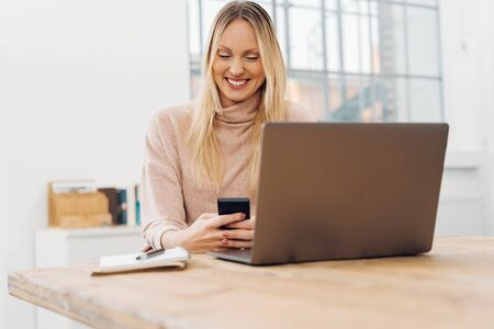 Businesswoman sitting at her desk in the office checking messages on her mobile phone with a pleased smile Stock Photo