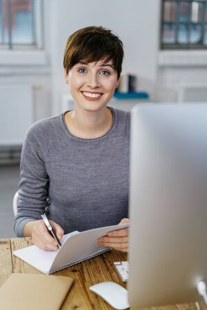 Happy young businesswoman writing at wooden desk on notepad with computer screen in foreground.