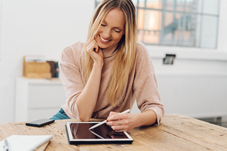 Cheerful blonde woman using digital tablet while sitting at table