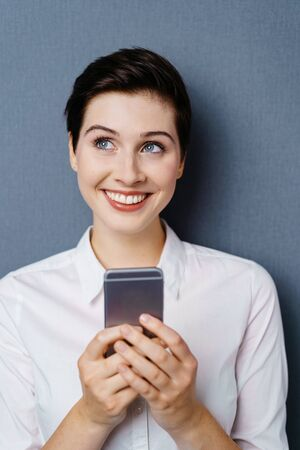 Thoughful happy young woman using mobile phone while standing against dark background