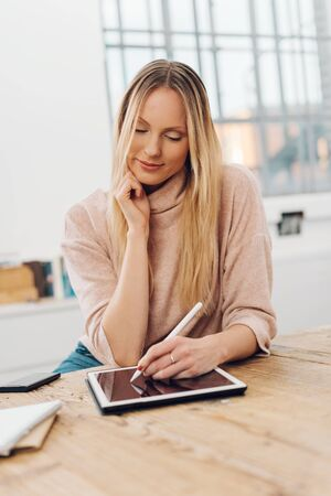 Young blonde woman using digital tablet while sitting at table Stock Photo