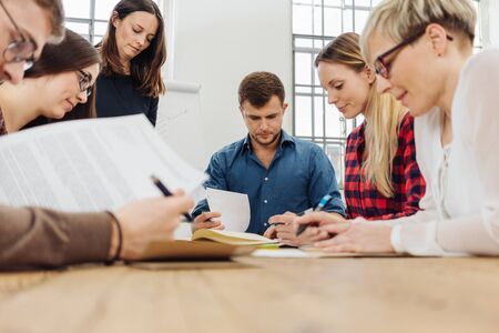 Group of businesspeople or students in a meeting working on paperwork grouped around a table in a low angle view