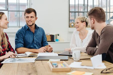 Diverse young business team in a meeting grouped around a table in an airy office having a discussion over paperwork