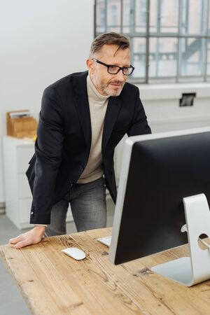 Businessman wearing glasses standing in a bright minimalist office reading a desktop monitor