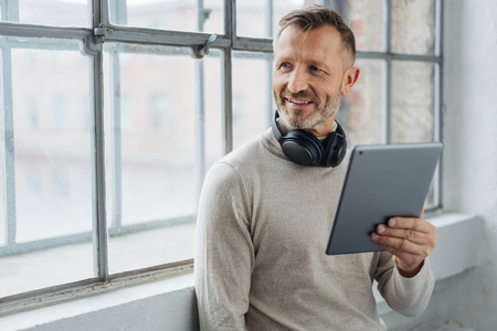 Smiling middle-aged man looking to the side as he stands leaning against the sill of a large window holding a tablet with headphones around his neck