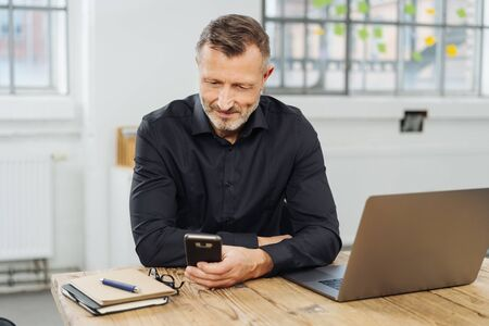 Businessman sitting checking his mobile phone for text messages with a smile at an office table Stock Photo