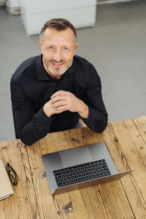 Businessman at an office table with a laptop sitting looking up at the camera with a smile