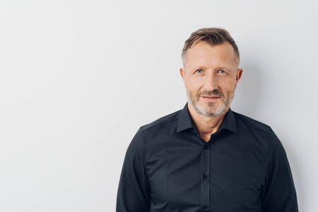 Head and shoulders portrait of a bearded middle-aged man looking thoughtfully at the camera over a white studio background with copy space Stock Photo