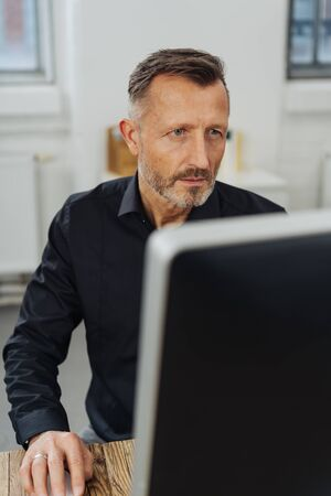 Concerned businessman staring at his desktop monitor with a focused intense look Banque d'images