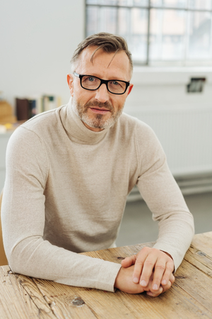 Confident stylish middle-aged man wearing glasses sitting at a table in a bright spacious room looking at the camera with an attentive serious expression