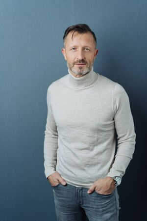 Serious middle-aged man staring at the camera with an intense watchful expression over a grey studio background