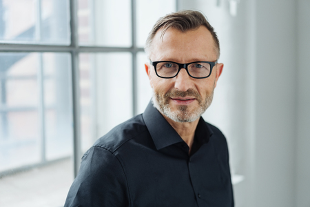 Close-up portrait of a middle-aged man wearing black shirt and eyeglasses while looking at camera with confidence in the office Stock Photo