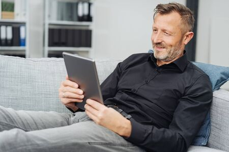 Relaxed middle-aged man reading an e-book on his tablet pc as he sits back on a comfortable sofa at home Banque d'images