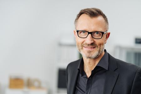Empresario de mediana edad con gafas sonriendo a la cámara en un retrato de cabeza y hombros con espacio de copia Foto de archivo