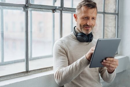 Man wearing stereo headphones around his neck browsing on a tablet in front of a window looking for a new soundtrack