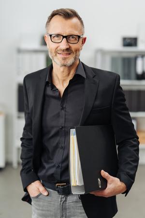 Sukcesy biznesmen niosący segregator biurowy pod pachą, gdy stoi, uśmiechając się do kamery z zamyślonym wyrazem twarzy Zdjęcie Seryjne