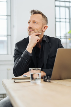 Middle-aged businessman deep in thought sitting at his desk with his hand to his chin staring up with a pensive expression