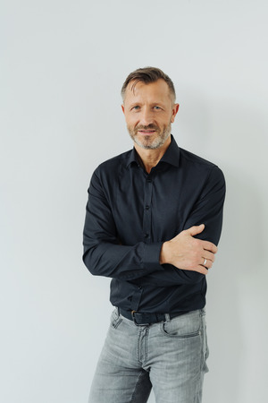 Confident relaxed middle-aged man standing with crossed arms and a quiet smile looking at the camera, three quarter portrait on a white wall background Stock Photo